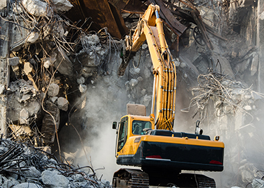 Demolition contractor uses Excavator with grapple and shear attachments to tear down building